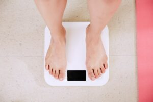 Woman stepping on a weighing scale